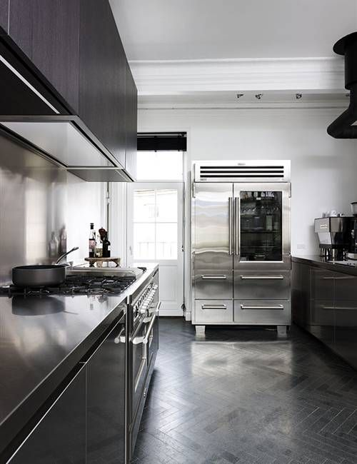 a sleek black kitchen with metal countertops, a large metal hearth and a sleek metal backsplash