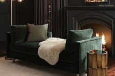 a sophisticated men's room with black walls and a fireplace, a mirror, some lamps, a side table and a green couch