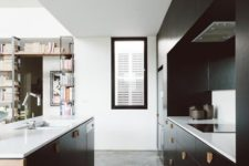 a stylish black kitchen with wooden handles, white countertops and a window to fill the space with light