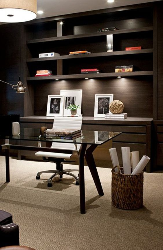 a stylish contemporary home office with a glass desk and a dark stained built-in shelving unit plus drawers and lamps