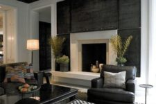 a stylish dark living room with a dark wall, a fireplace, dark furniture, a grey rug and a sleek black table