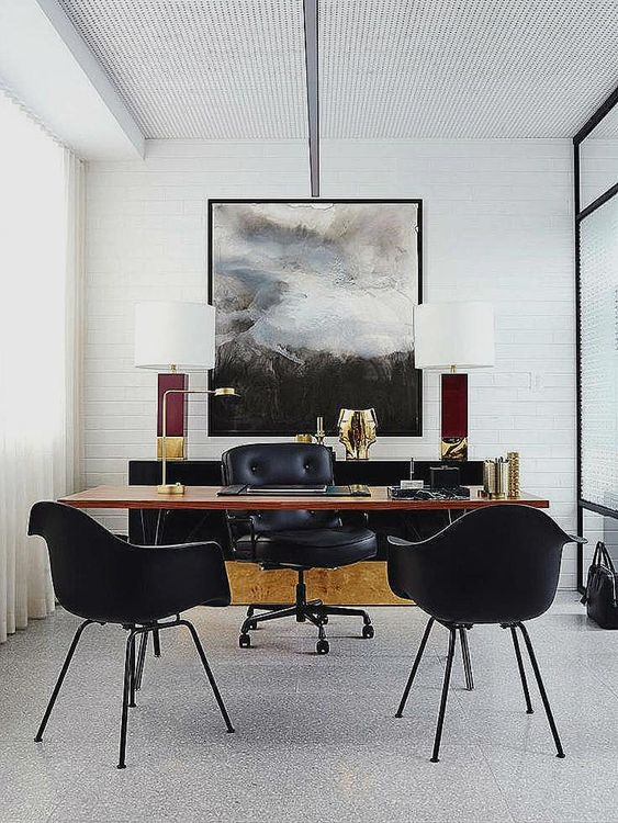 a stylish home office in neutrals with a black sideboard, a sleek wooden desk and black leather chairs for an elegant touch