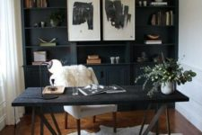 a stylish home office with white walls and a black built-in shelving unit, a black desk and a brown leather chair