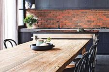 a stylish masculine kitchen with a red brick backsplash and black cabinets and pendant lamps