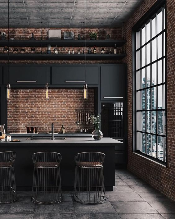 a stylish moody kitchen with black cabinets, gold touches, a large kitchen island and red brick walls