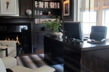 a super chic masculine home office with dark built-in shelves, a fireplace, a dark desk and creamy upholstered chairs