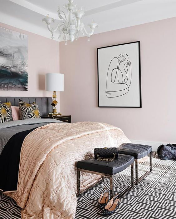 a super stylish feminine bedroom with light pink walls, a grey bed, black woven stools, a statement artwork and touches of gold