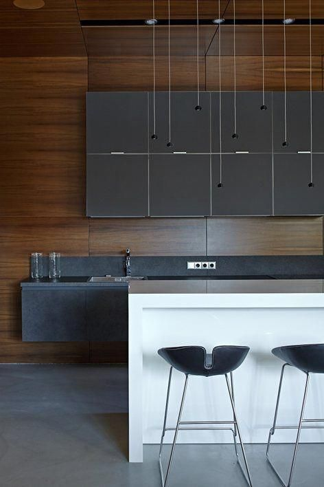 a super stylish minimalist kitchen with matte grey cabinets, stone countertops, a white kitchen island plus black stools