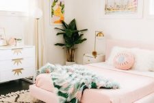 a tropical girlish bedroom with a pink floating bed, a printed rug and bedding, bold artworks and touches of gold