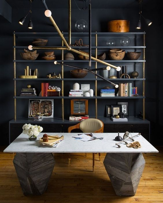 a unique home office with blakc walls, an open shelving unit, a sculptural stone desk and a unique metal chandelier