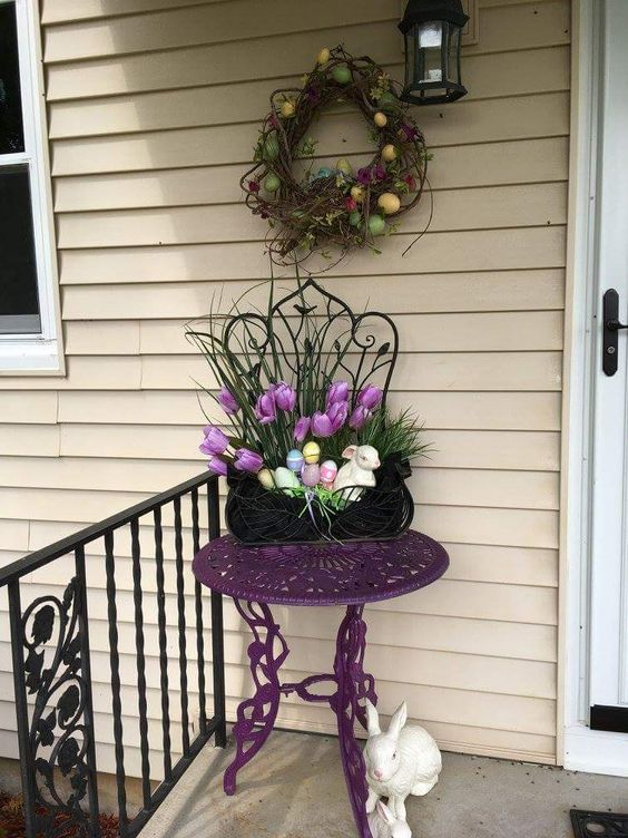 a vine wreath with colorful eggs, potted blooms and faux eggs in a planter, fake bunnies for porch decor