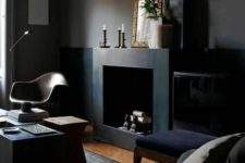 a welcoming dark manly room with black walls, a fireplace, some dark upholstered furniture, lamps and candles