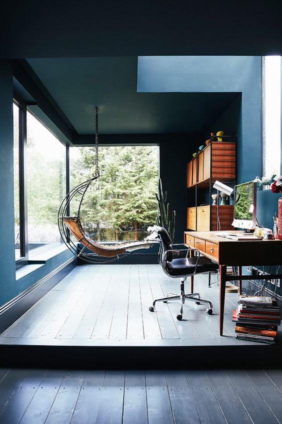 a welcoming home office in blue, with panoramic windows and a skylight, a wooden desk plus a leather chair, a hanging lounger and a shelving unit