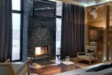 a welcoming living room with wooden beams, a brick clad fireplace, dark furniture and lights
