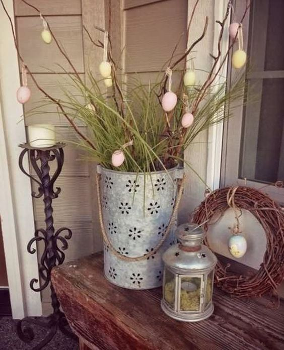 a wreath with a hanging egg and a laser cut bucket with branches, grass and colorful eggs