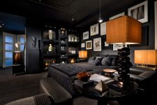 all black bedroom with an interesting art wall and very thoughtful lighting