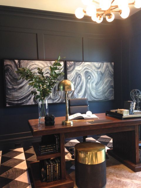 an art deco home office with marble artworks, navy walls, a rich stained desk with storage and gilded touches
