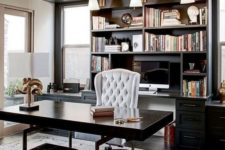 an elegant and chic masculine home office with a wooden desk and a stool, a built-in bookcase and much natural ligjt