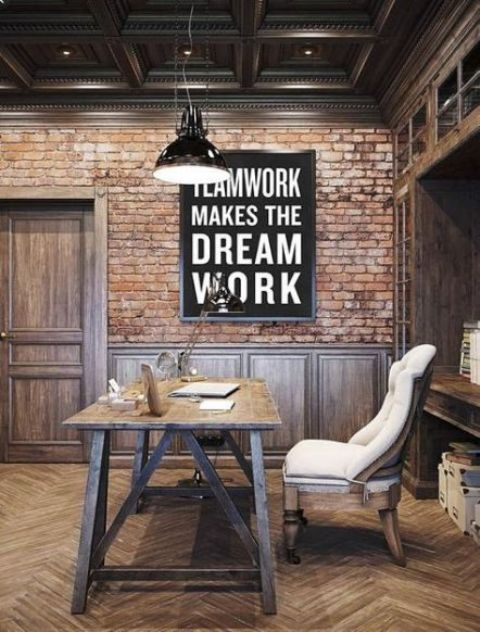 an industrial home office with brick walls, a built-in shelving unit, a wooden desk and a comfy upholstered chair