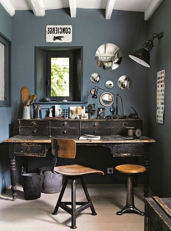 an industrial home office with grey walls, an arrangement of mirrors, a shabby chic wooden desk and industrial chairs