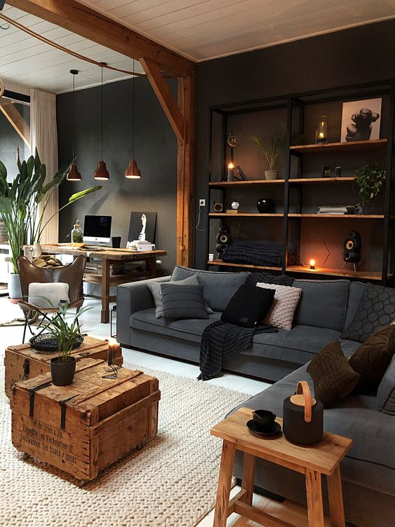 an industrial living room with a wall-mounted shelving unit, grey upholstery, wooden chests and a stool and workspace in the corner