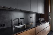 an ultra-minimalist kitchen with sleek black and rich-stained cabinets plus a sleek countertop plus a stone backsplash