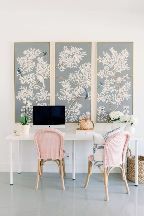 beautiful light blue flora and fauna artworks and pink chairs make the home office spring-like