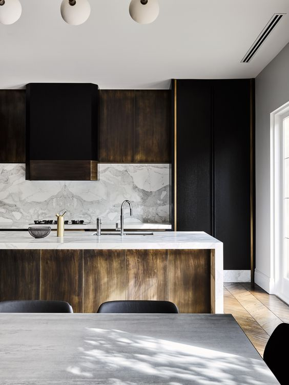 black and light-colored wooden cabinets, a marble backsplash and countertops for a chic touch