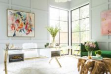 bright artworks, a green sofa and some greenery in a vase make the home office feel spring-like