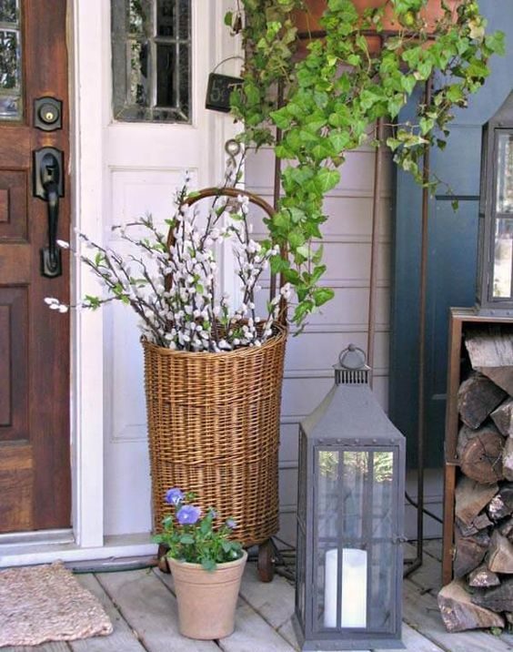 chic Easter porch decor with potted flowers, pussy willow in a basket and a large candle lantern