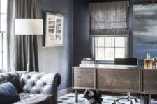 elegant grey and blue home office with a wooden desk, fabric curtains and shades, a leather sofa and a plaid rug