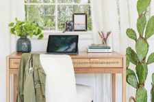 greenery in a vase and a large cactus in a pot refresh the space and make it more bright and welcoming