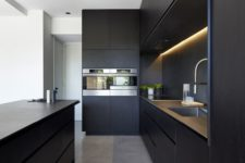 matte sleek kitchen cabinets, built-in lights, stone countertops and built-in appliances for elegant chic