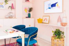 pink walls, a bright blue chairs, bright artworks and a bold rug make the space feel fun and spring or summer