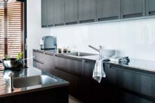 rich stained wooden cabinets, a white backsplash and metal countertops plus shutters for a private feel