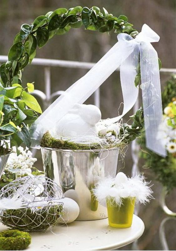 simple Easter decor with a bucket with greenery, a bow, some faux eggs and decorative ones