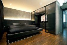 urban bedroom with gray walls and dark hardwood floors with a walk-in closet behind glass doors