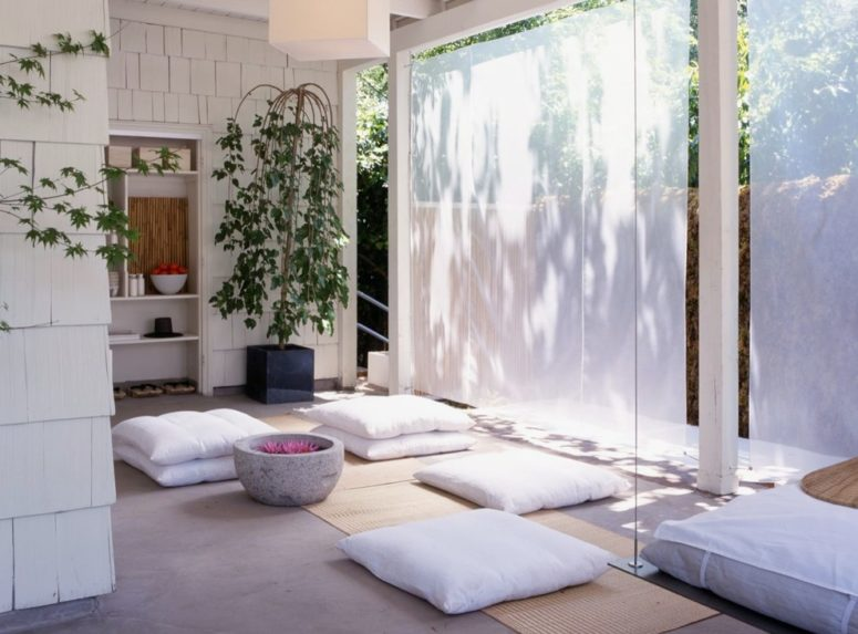 a neutral meditation space with white pillows, potted greenery and screens to avoid excessive light  (Rozalynn Woods Interior Design)