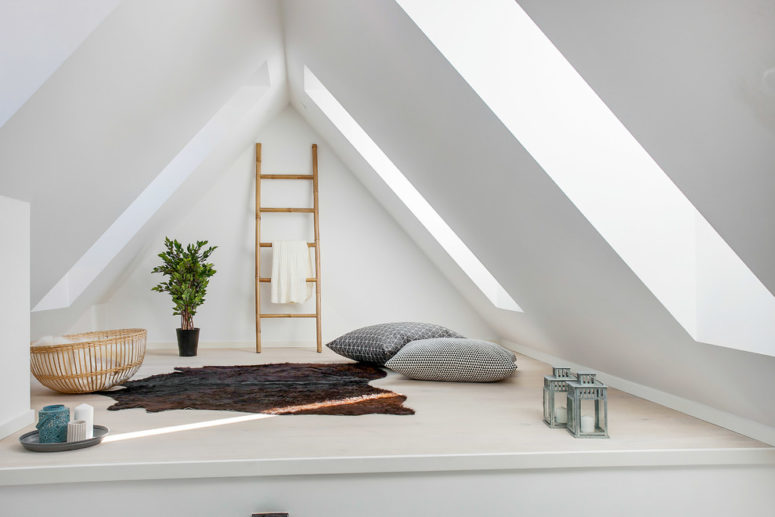 a small and minimalist attic space with a rug, pillows and candle lanterns  (Busy Bees ApS)