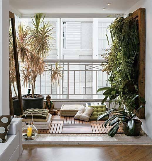 a balcony turned into a meditation space with cushions and rugs plus a lush greenery wall