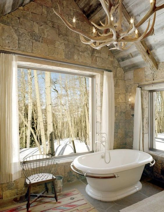 a barn bathroom clad with stone, a panoramic window, an antler chandelier, a free-standing tub and a bright rug