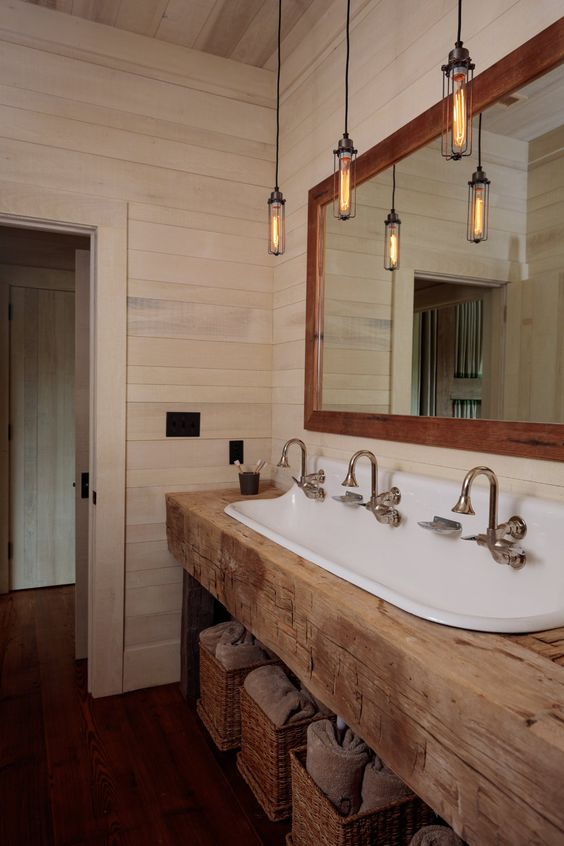 a barn bathroom clad with whitewashed wooden planks, with a rough wooden vanity, pendant lamps and baskets for storage