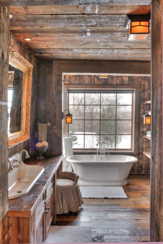 a barn bathroom decorated with rough weathered wood, with a large window, a wooden vanity and a free-standing tub