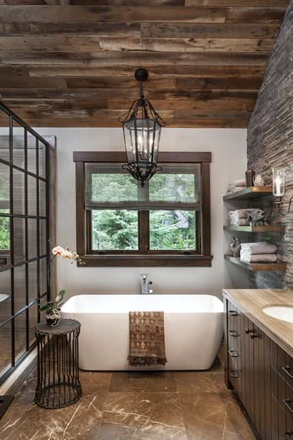 a barn bathroom with a reclaimed wooden ceiling, a tile floor, a stoen enclosed shower and a vintage lantern hanging down