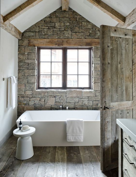 a barn bathroom with a stone wall, a wooden floor and wooden beams, a free-standing tub, a window for natural light