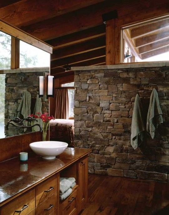 a barn bathroom with a stone wall, stained wood everywhere and a large mirror plus a bowl sink