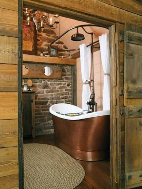 a barn bathroom with a stone wall, wood plank walls, a metal tub and vintage chandeliers plus a jute rug