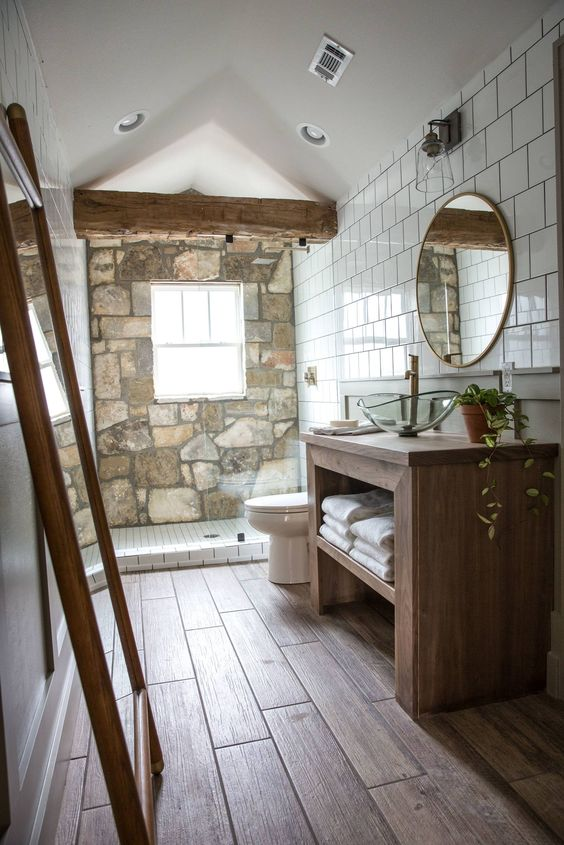 a barn bathroom with a stone wall, wooden beams, a wooden vanity, mirrors and white tiles on the wall