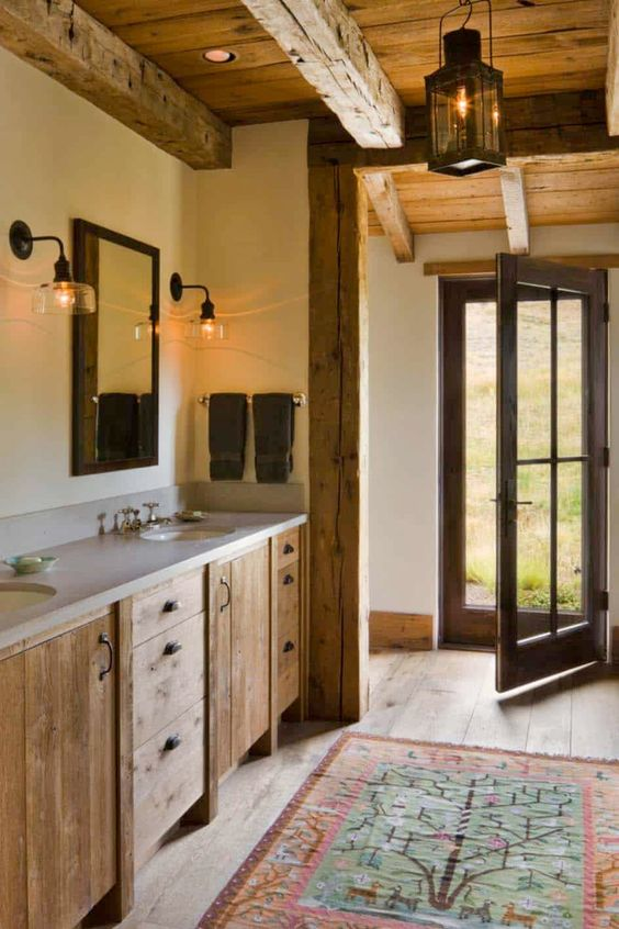 a barn bathroom with a wooden ceiling with beams, a wooden vanity, a stone countertop and vintage wall lamps