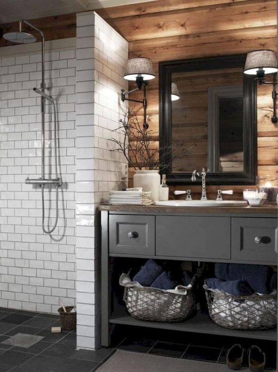 a barn bathroom with a wooden wall, a vintage grey vanity, a white tile clad shower space and a mirror in a black frame
